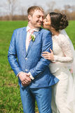 Happy bride kissing smiling groom to cheek. On nature Royalty Free Stock Image