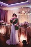 Happy bride with a large bouquet of roses. beautiful young smiling bride holds large wedding bouquet with pink roses royalty free stock photo