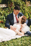 Happy bride lays on groom's legs on grass in park Royalty Free Stock Images