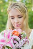 Happy bride looking at her bouquet Royalty Free Stock Photography