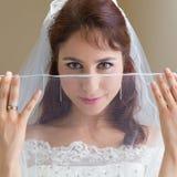 Happy bride looking through sheer veil Stock Images