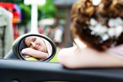 Happy bride looks in mirror of car at wedding walk royalty free stock photo