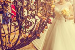Happy bride near metal tree with symbol lock at a wedding a walk in KlaipÄ—da Lithuania. Vintage tone. Happy bride near metal tree with symbol lock at a stock images