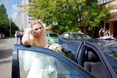 Happy bride near wedding car Stock Images