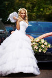 Happy bride near wedding car Royalty Free Stock Images