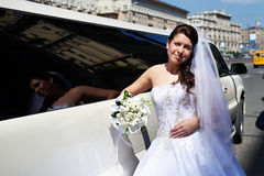 Happy bride near wedding limo. On sunny day Royalty Free Stock Photography