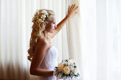 Happy bride near window with flowers royalty free stock images