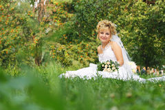 Happy bride at a park in grass Stock Photos