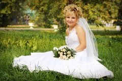 Happy bride at a park in grass Stock Photo