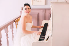 Happy bride playing the piano Royalty Free Stock Image