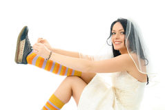 Happy bride putting on sporting shoes Royalty Free Stock Photos