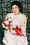 Happy bride with red bouquet in cane chair Stock Image