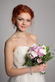 Happy bride with red hair on gray Royalty Free Stock Image