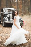 Happy bride in the retro car posing on her weeding day Stock Image