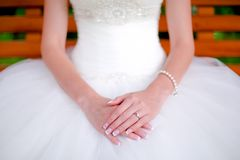 Happy bride showing hands and jewelry on wedding dress Stock Photo