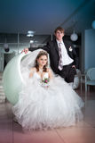 Happy bride sit in fancy chair and groom stand near chair Royalty Free Stock Image