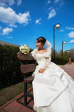 Happy bride sits on a bench Royalty Free Stock Photography