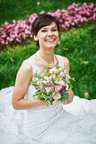 Happy bride sitting on grass at wedding walk Royalty Free Stock Image