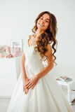 Happy bride smiling at the camera. Wedding hairstyle and make up. Stock Photos