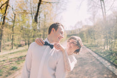 Happy bride standing behind fixing blue bow tie of her smiling groom in white shirt Stock Photo