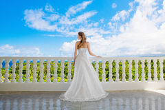Happy bride standing next to the stone gazebo amid beautiful tro Royalty Free Stock Images