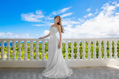 Happy bride standing next to the stone gazebo amid beautiful tro Stock Photography