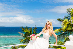 Happy bride standing next to the stone gazebo amid beautiful tro Royalty Free Stock Photography
