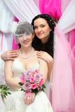 Happy bride stands behind other bride Stock Images