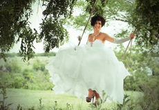 Happy bride on the swings, countryside background Royalty Free Stock Images
