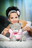 Happy bride with teddy bear on white bed Royalty Free Stock Photos