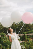 Happy bride with three balloons on nature Royalty Free Stock Photography