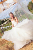 Happy bride twirling in wedding dress. Stock Photo