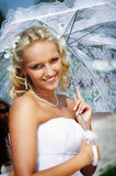 Happy bride with umbrella in wedding walk Stock Image