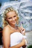 Happy bride with umbrella in wedding walk Stock Image