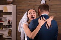 Happy bride in veil embracing groom in suit Royalty Free Stock Photos
