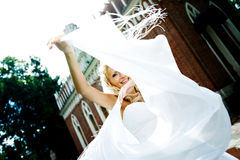 Happy bride with veil fluttering in park Royalty Free Stock Photos