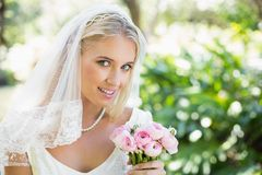 Happy bride in a veil holding her bouquet looking at camera Stock Photos