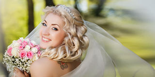 Happy bride in a veil holding her bouquet looking at camera in the countryside Stock Photos