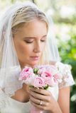 Happy bride in a veil smelling her rose bouquet Stock Photos