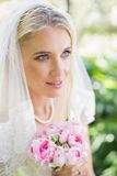 Happy bride wearing veil holding bouquet looking away. In the countryside Royalty Free Stock Image