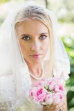 Happy bride wearing veil holding bouquet looking at camera. In the countryside Royalty Free Stock Photos
