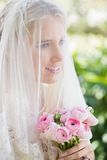 Happy bride wearing veil over face holding rose bouquet. In the countryside Royalty Free Stock Photo