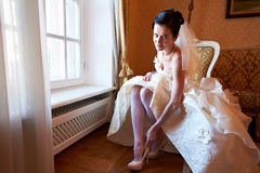 Happy bride wears her shoes Royalty Free Stock Photo