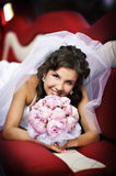 Happy bride with wedding bouquet in limo Stock Photos
