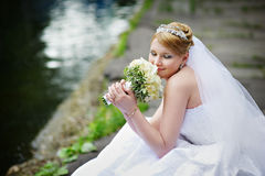 Happy bride in wedding dress with bouquet. Happy bride in wedding dress near lake with bouquet of flowers Royalty Free Stock Images