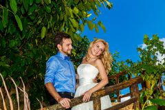 Happy bride in the wedding dress and groom smiling tropical plan Royalty Free Stock Image