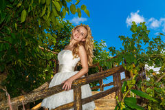 Happy bride in wedding dress smiles tropical plants in the backg Stock Image