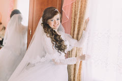Happy bride in wedding dress and veil near sunny window royalty free stock images