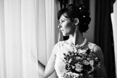 Happy bride with weding bouquet near window Royalty Free Stock Photo