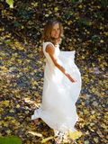 Happy bride in white dress in autumn defoliation. Happy bride in white dress in autumn park among fallen leaves Royalty Free Stock Photos
